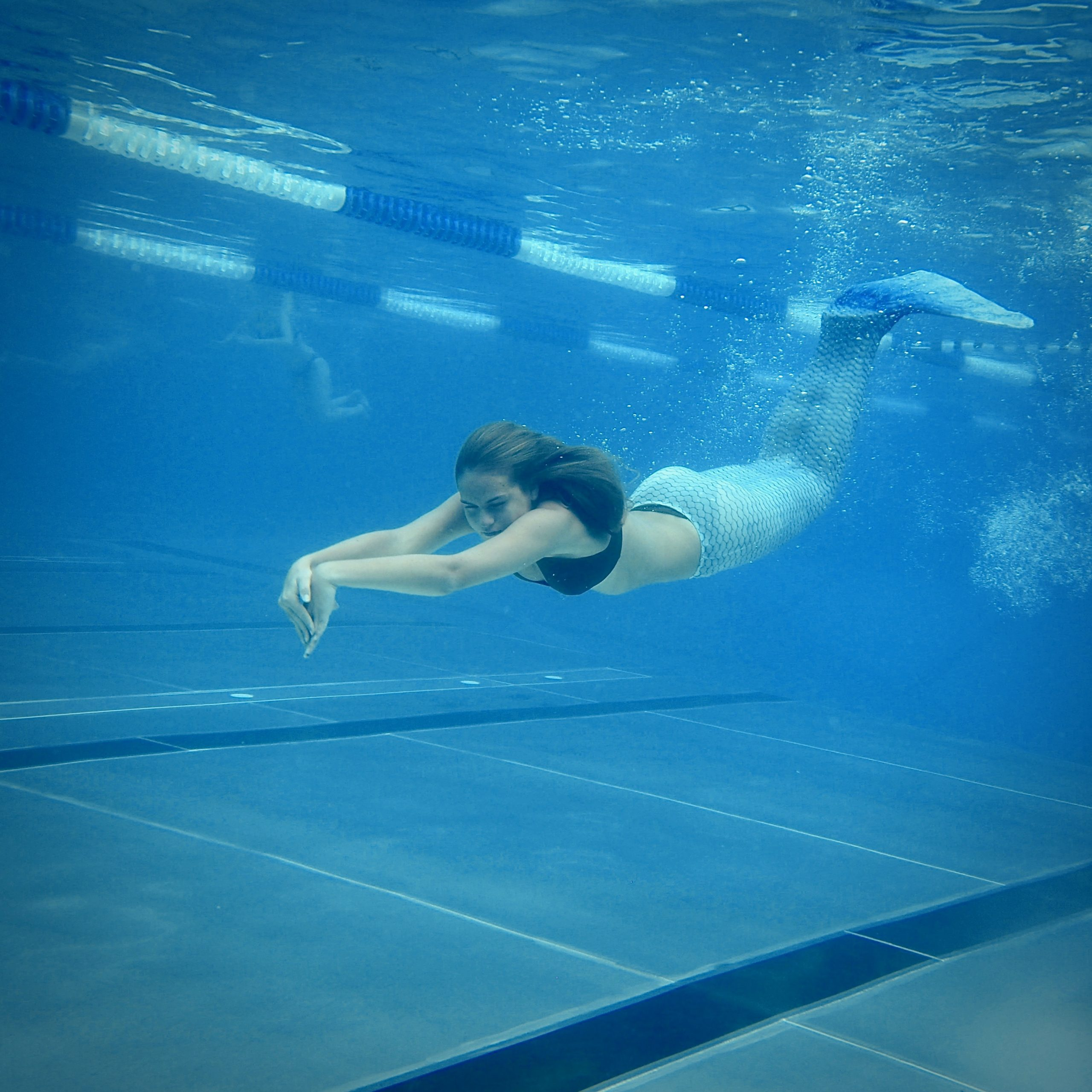 Meerjungfrau taucht im Schwimmbad