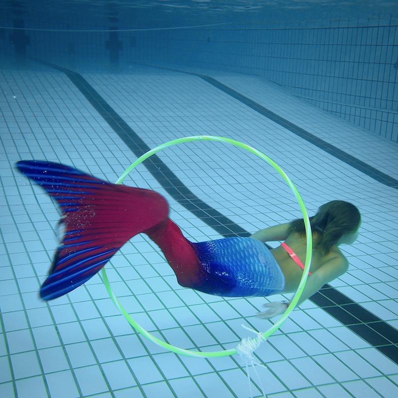 Little Mermaid Meerjungfrau taucht durch Reifen im Schwimmbad