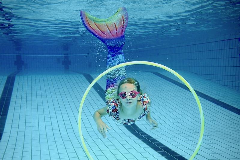 Mermaid Meerjungfrau taucht durch Reifen im Schwimmbad