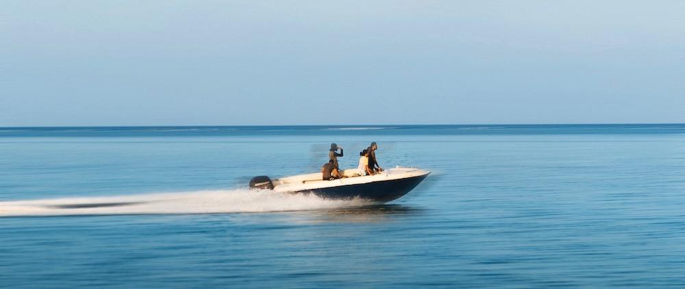 Motorboot auf Meer in voller Fahrt mit Crew