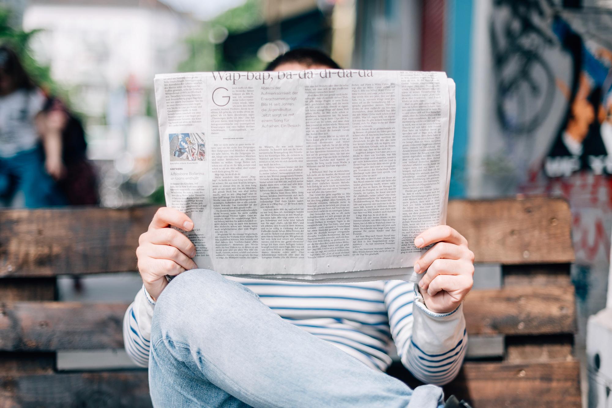 Person mit News Zeitung auf Bank
