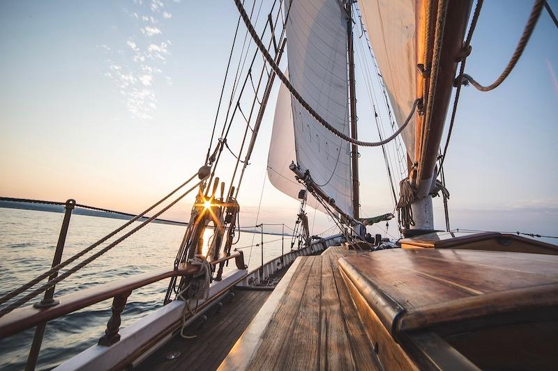 Segelboot bei Sonnenuntergangsstimmung an Kueste