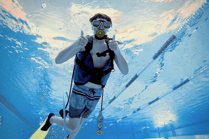 Taucher unter Wasser im Schwimmbad mit Daumen hoch